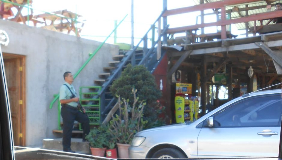 Guard carrying a slung pistol gripped shotgun outside of San Salvador restaurant.