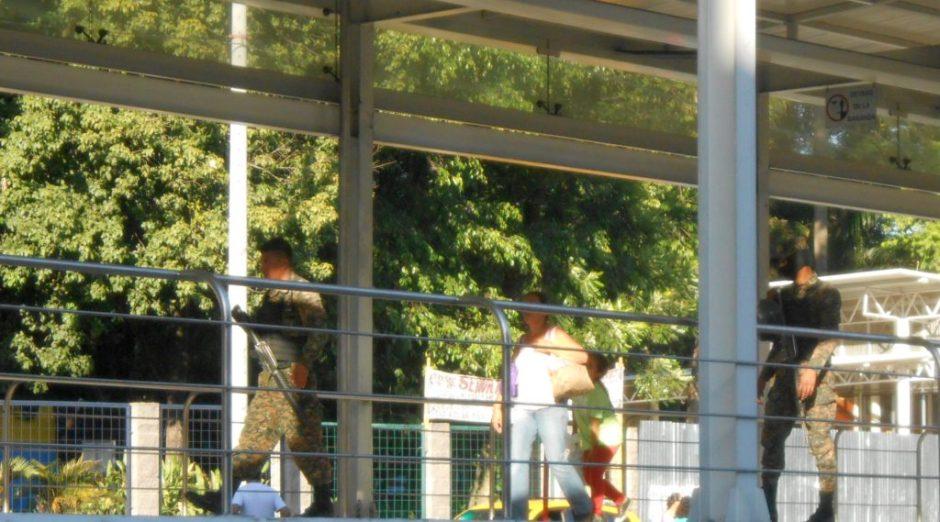 Soldiers patrolling a San Salvador bus stop,
