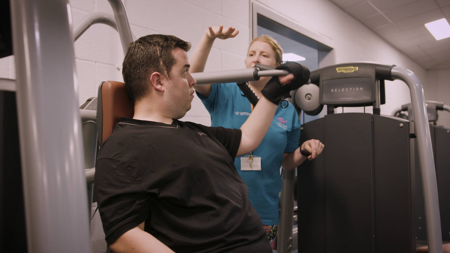 Persion instructing supporting disabled man in a gym