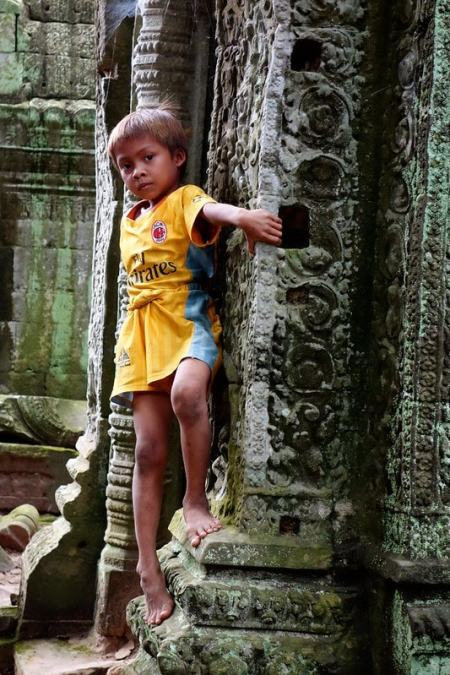 Kid playing on temples Angkor Wat