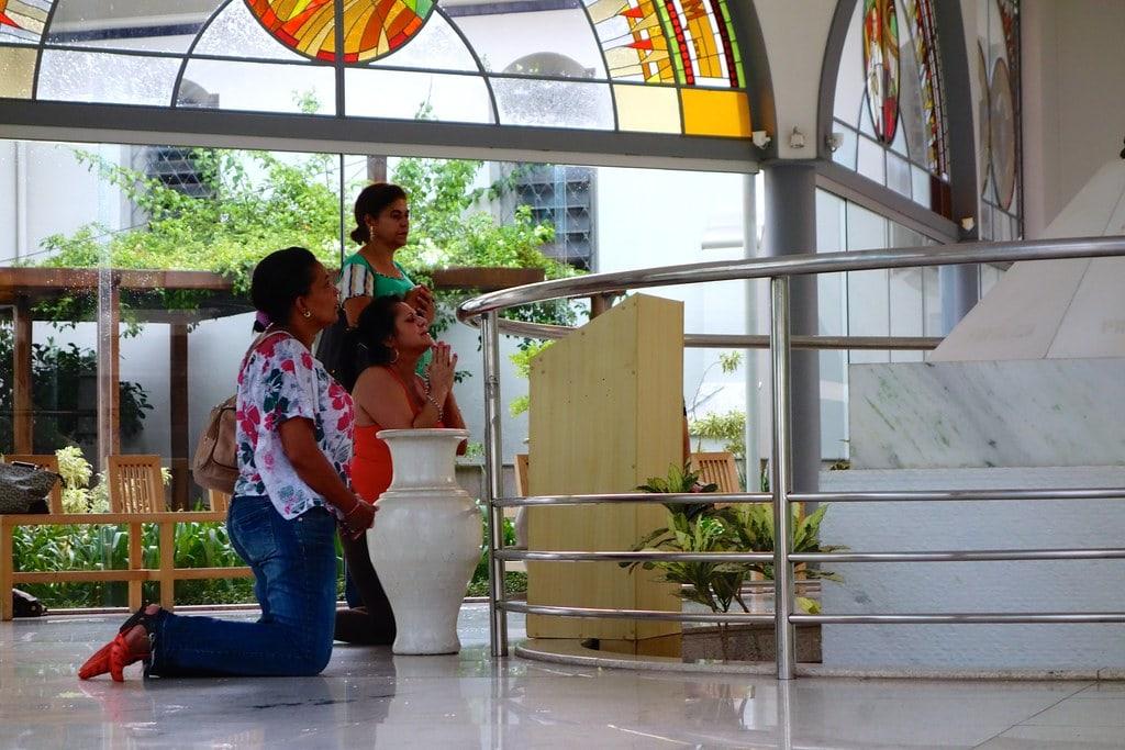 Kneeling near tomb Padre Eustaquio