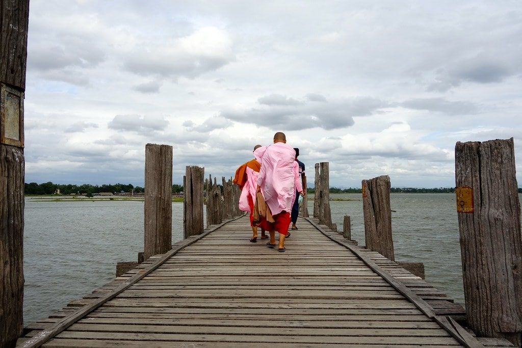Monks walking on a wooden bridge