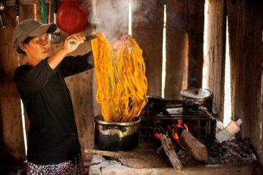 María Tamani hierve las fibras de la chambira (Astrocaryum chambira) con cúrcuma (Curcuma longa) para teñirlas de amarillo. Para obtener el color anaranjado, utiliza el achiote (Bixa orellana), y para el color negro, el fruto del huito (Genipa americana).