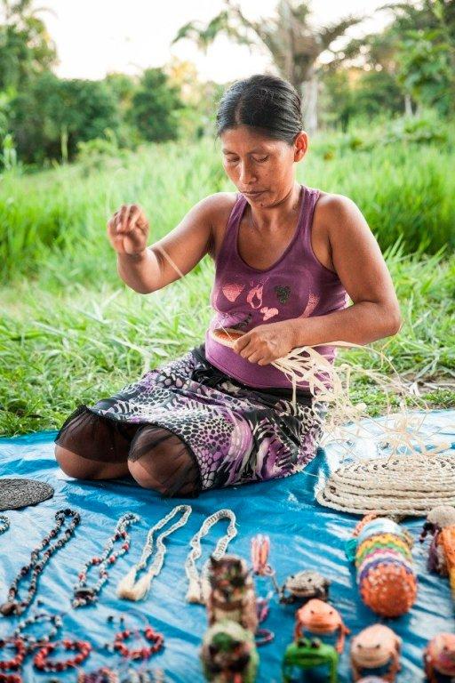 María Tamani teje una panera con chambira, mientras ofrece sus productos a los turistas que visitan Puerto Prado para conocer el estilo de vida de los pobladores de la ribera del Marañón.