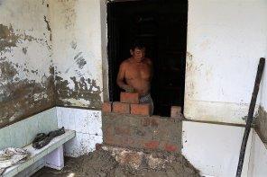 Algunas personas se resistieron a salir de sus viviendas y esperar la inundación, como este señor que tapiaba la puerta de su casa.