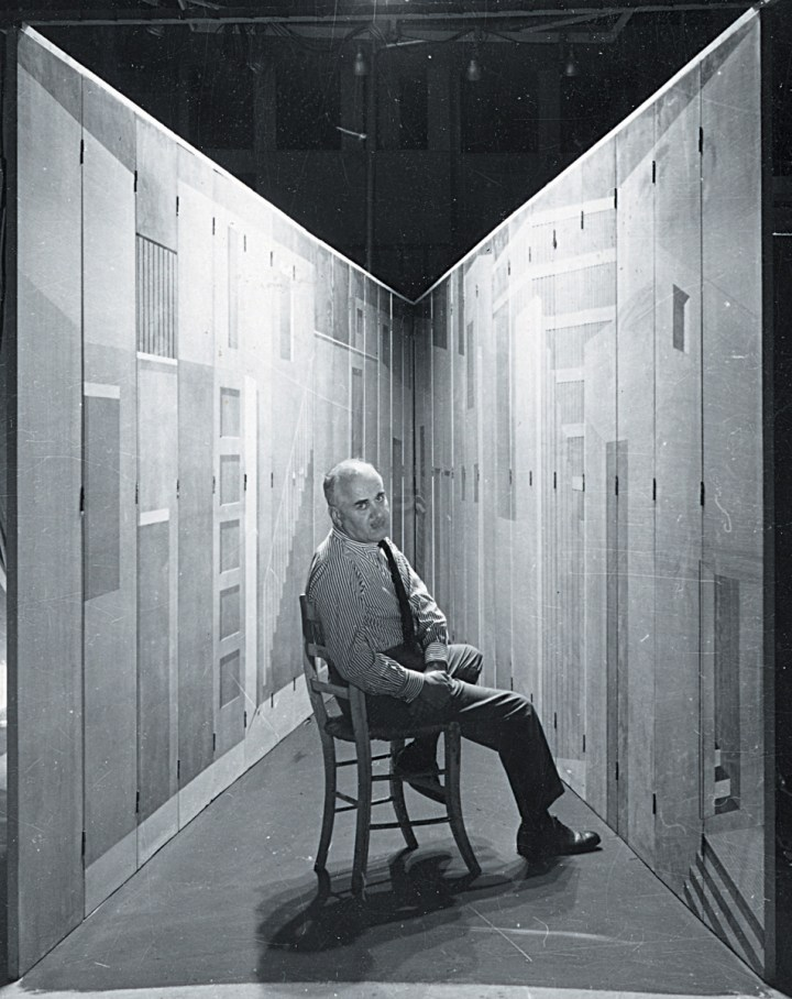 "Piero Fornasetti with his ""Stanza Metafisica"" (Metaphysical Room). Presented for the first time in an exhibition organized at the Tea Center of London in 1958, this work is composed of thirty-two panels. The structure can be set up in various ways to create a setting suitable for meditation. Courtesy Fornasetti"