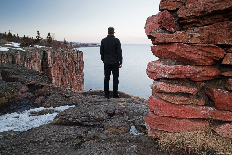 Man standing on the edge at Palisade Head - snow on rocks