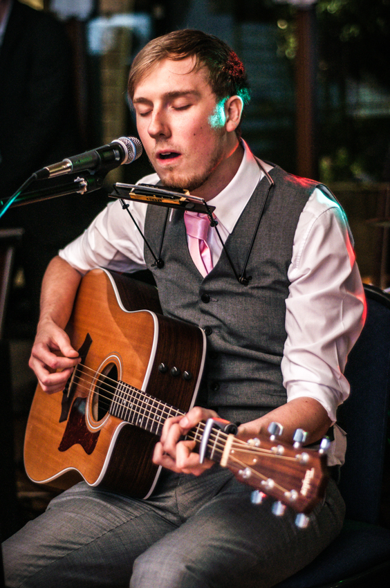 Groom plays the acoustic guitar while singing Dustin Kensue