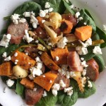 A plate of salad with spinach, sausages, roasted vegetables, and feta