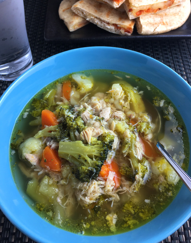 A blue bowl of Oh So Good Chicken Vegetable Soup containing carrots, broccoli, cauliflower, and chicken