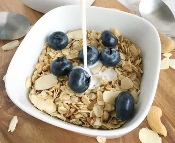 Milk being poured into a white bowl containing nutty granola and 7 blueberries