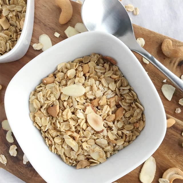 A spoon next to a square white bowl containing nutty granola