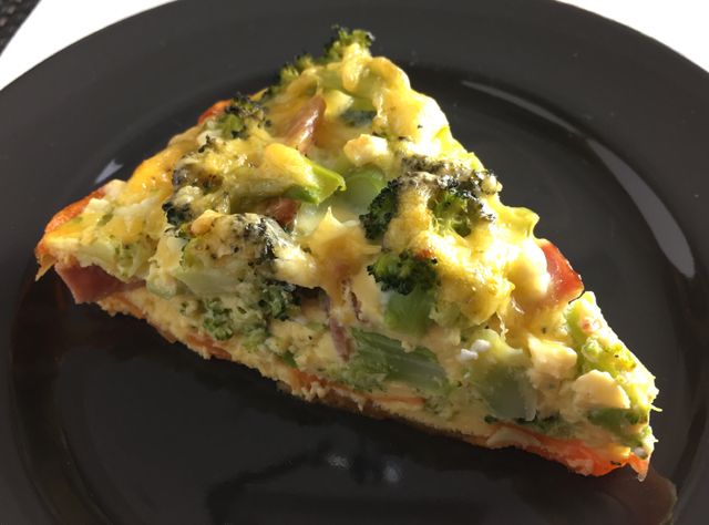 A piece of Sweet Potato Broccoli Bacon Quiche on a black plate