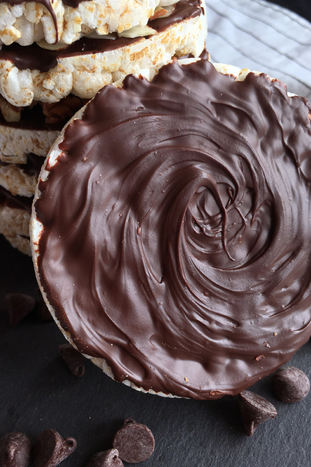 Close-up of a chocolate coated rice cake leaning against a stack of chocolate coated rice cakes