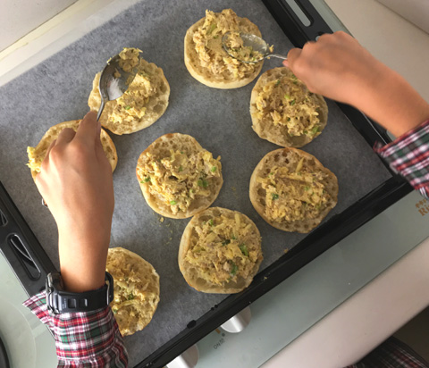 A child's hands, scopping curry chicken topping onto English muffins on a baking sheet for Curry Chicken Canapes