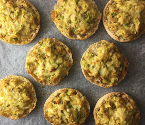 Curry Chicken Canapes made of English muffin halves with curry chicken topping on a baking sheet