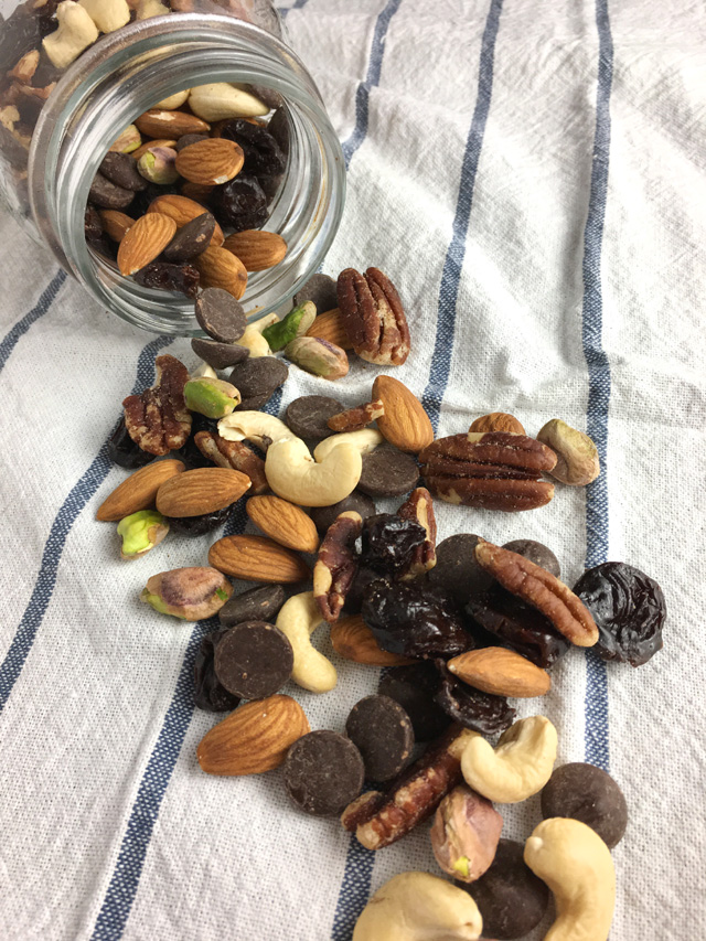 DIY Salty & Sweet Trail Mix pouring out of a glass jar onto blue and white striped cloth
