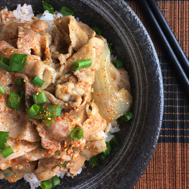 Japanese Butadon Pork Bowl containing pork, onions, green onions, and rice
