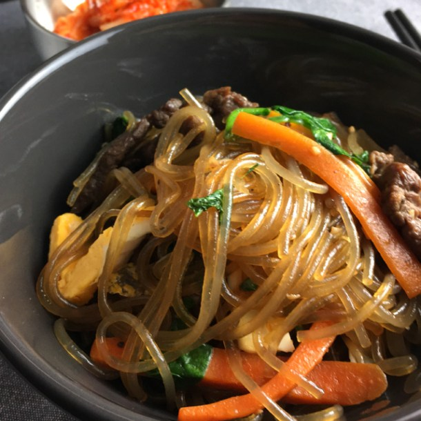 A small bowl of Korean Sweet Potato Noodles Japchae including carrots, beef slices, scrambled eggs, and spinach Best of 2017
