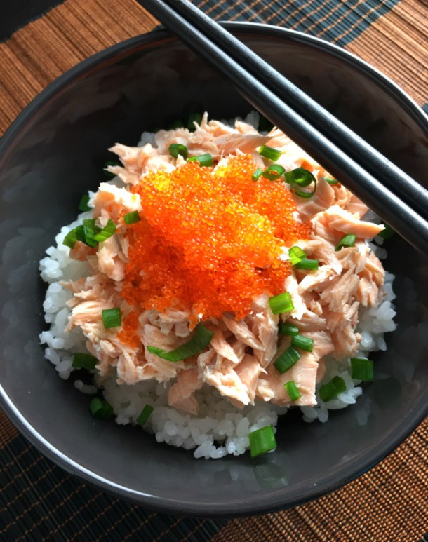 A Poached Salmon Tobiko Bowl containing white rice, salmon, fish eggs, and chopped green onions