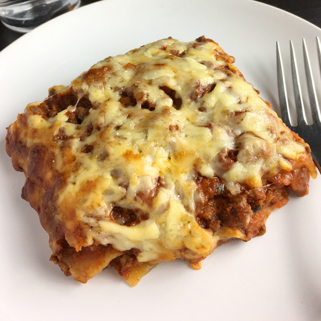A piece of lasagna on a plate with a fork