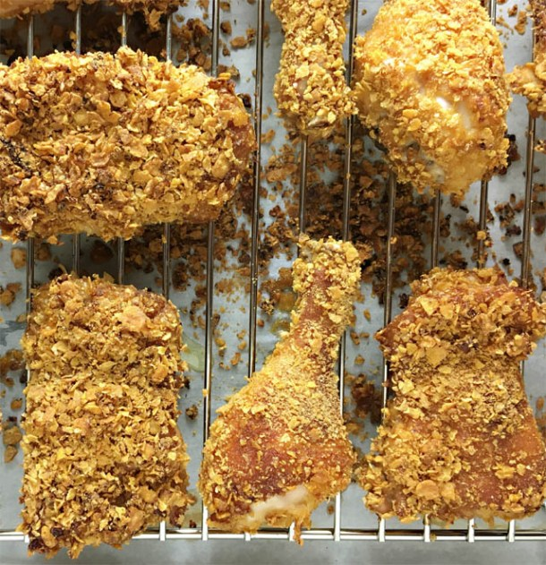 Cornflakes chicken on a metal rack on a baking sheet
