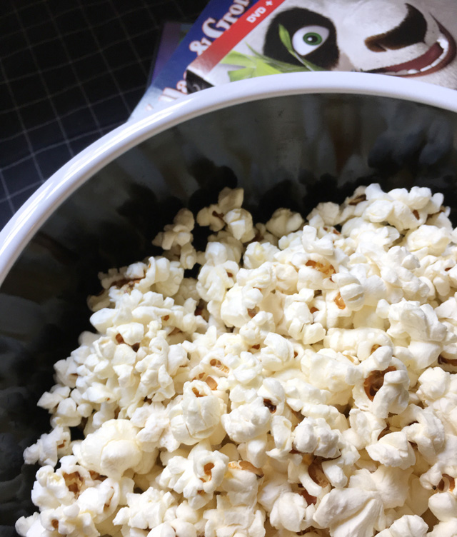 A black and white bowl of Easy Perfect Stovetop Popcorn with DVD cases in the background