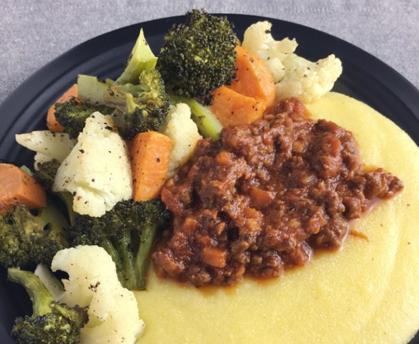 A black plate with roasted vegetables and Beefy Tomato Bolognese Sauce on polenta