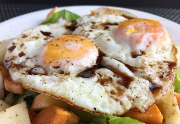 Close-up of two sunny-side up eggs over roasted vegetables for Crispy Fried Eggs Over Veggies