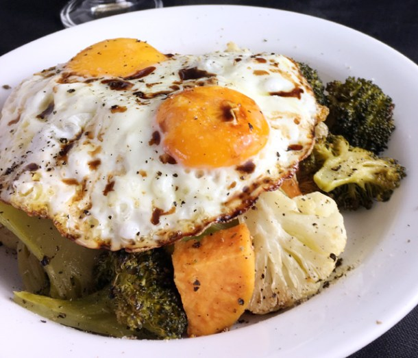 A white plate containing two crispy fried eggs and roasted vegetables from Crispy Fried Eggs Over Veggies