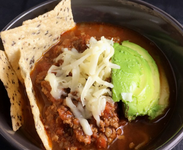 A bowl of Chunky Chipotle Chili Con Carne with tortilla chips, avocado slices and grated cheese