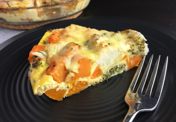 A wedge shaped piece of Crustless Roasted Vegetable Quiche on a black plate with a fork
