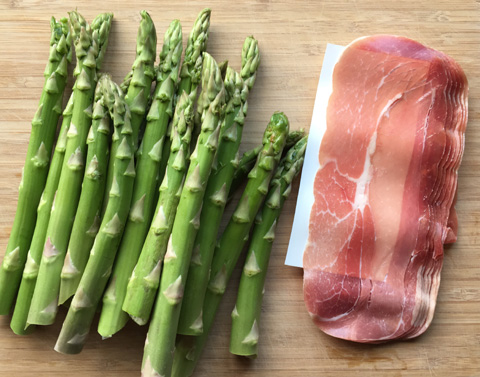 Raw asparagus and prosciutto on a wooden cutting board for Prosciutto Wrapped Asparagus