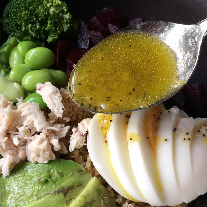 Close-up of a spoonful of orange dressing being drizzled over a bowl containing sliced egg, avocado, chicken, edamame beans
