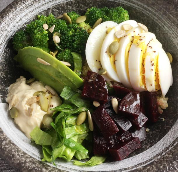 Super Food Quinoa Bowl containing hummus, lettuce, avocado, beets, hard boiled egg, broccoli, and sunflower and pumpkin seeds