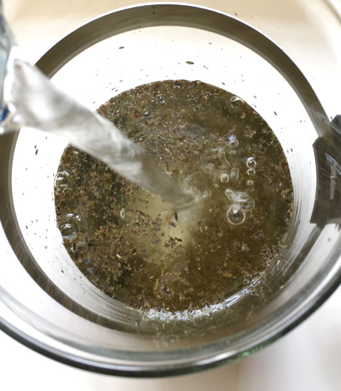 Water pouring into a carafe containing loose tea leaves to make Cold Brewed Tea