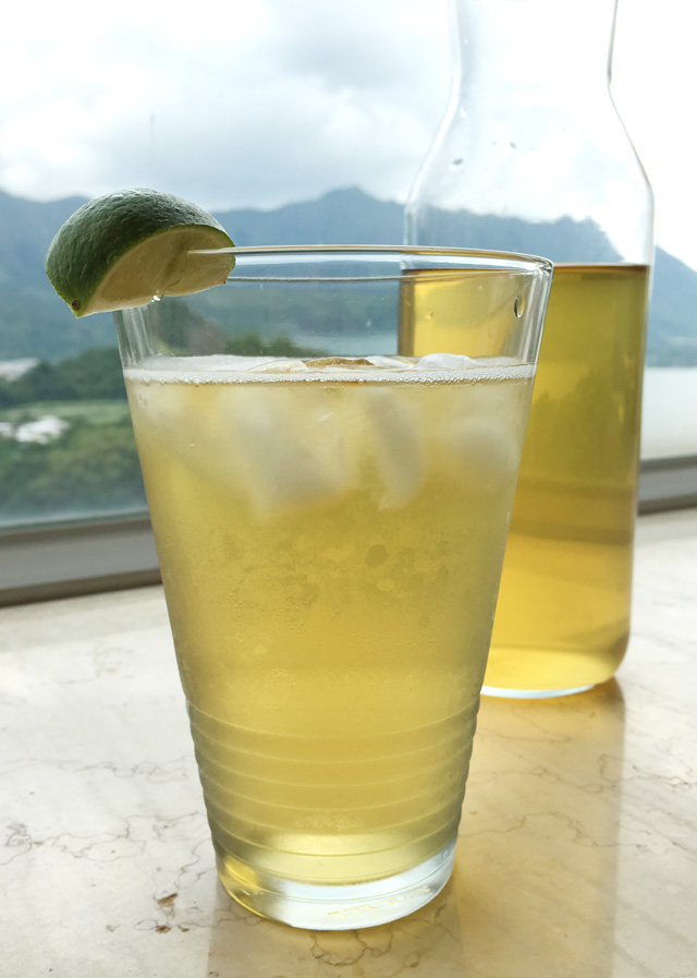 A glass containing Cold Brewed Tea with ice cubes and a lime wedge garnish