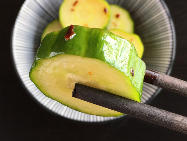 A close-up of chopsticks holding a cucumber slice from Cold Spicy Cucumber Bites
