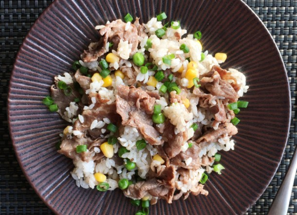 A brown plate of Pepper Beef Rice Skillet containing rice, beef, corn, and peas
