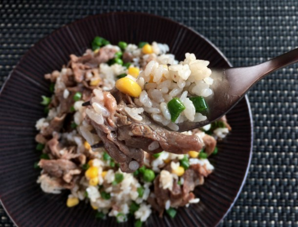 A forkful of rice, beef, corn, and peas from a plate of Pepper Beef Rice Skillet