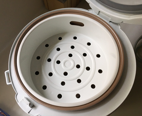A white steaming tray in a rice cooker to make Eggs in a Rice Cooker