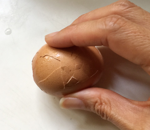 Cracking the brown shell of a hard cooked egg on the counter. Cook Eggs In A Rice Cooker