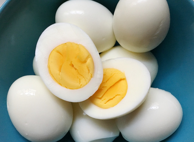 A hard-boiled egg cut in half on other hard boiled eggs from cooking Eggs In A Rice Cooker