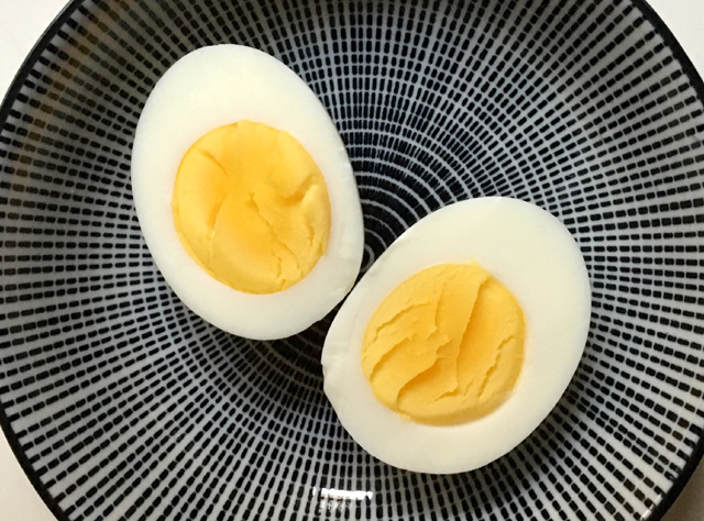 Hard cooked egg cut in half on a round plate. Cook Eggs In A Rice Cooker
