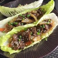Three Korean Steak Lettuce Wraps on a brown metallic plate