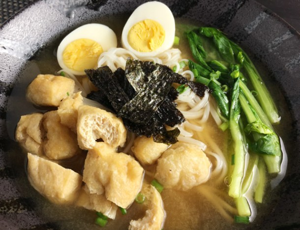 A black bowl of Miso Noodle Soup containing tofu puffs, hard cooked eggs, rice noodles, Asian green vegetables, roasted seaweed and soup.