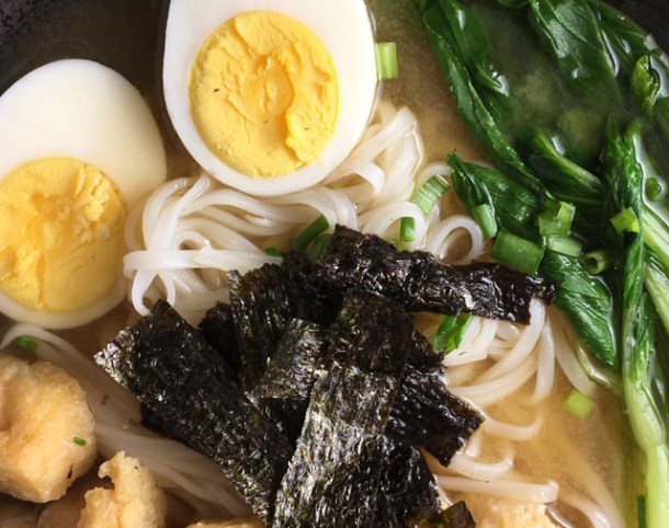 Miso Noodle Soup containing rice noodles, hard cooked egg, leafy green vegetables, tofu puffs, and roasted sewaeed
