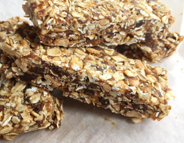 A pile of Simple Nutty Granola Bars made from rolled oats, nuts, chocolate chips, and dates