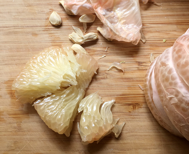 Peeled pomelo wedges on a wooden cutting board