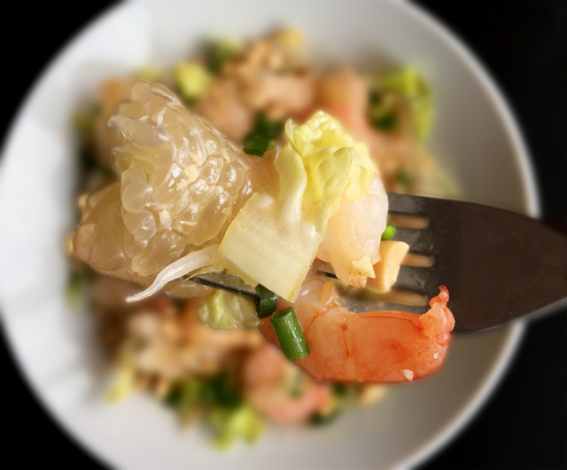 Closeup of a pomelo wedge, lettuce, and shrimp on a fork